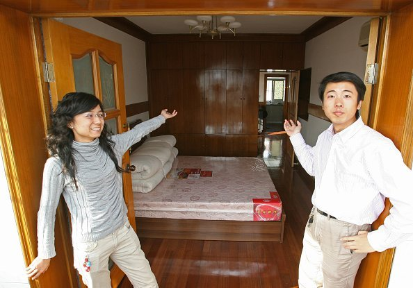 A couple standing in front of their newly bought home   Photo: Getty Images