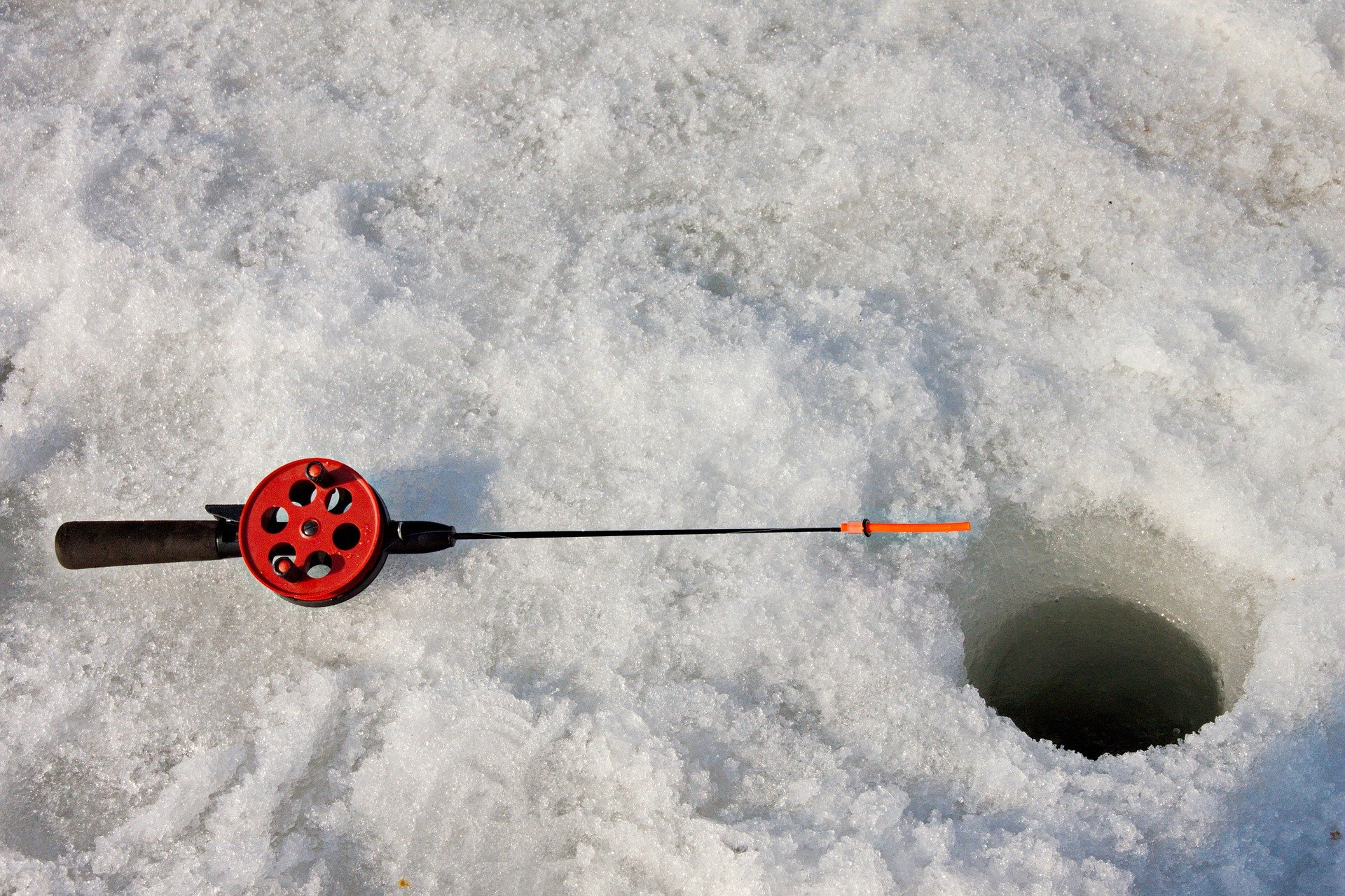 A hole in the ice with a fishing rod next to it.   Source: Pixabay.