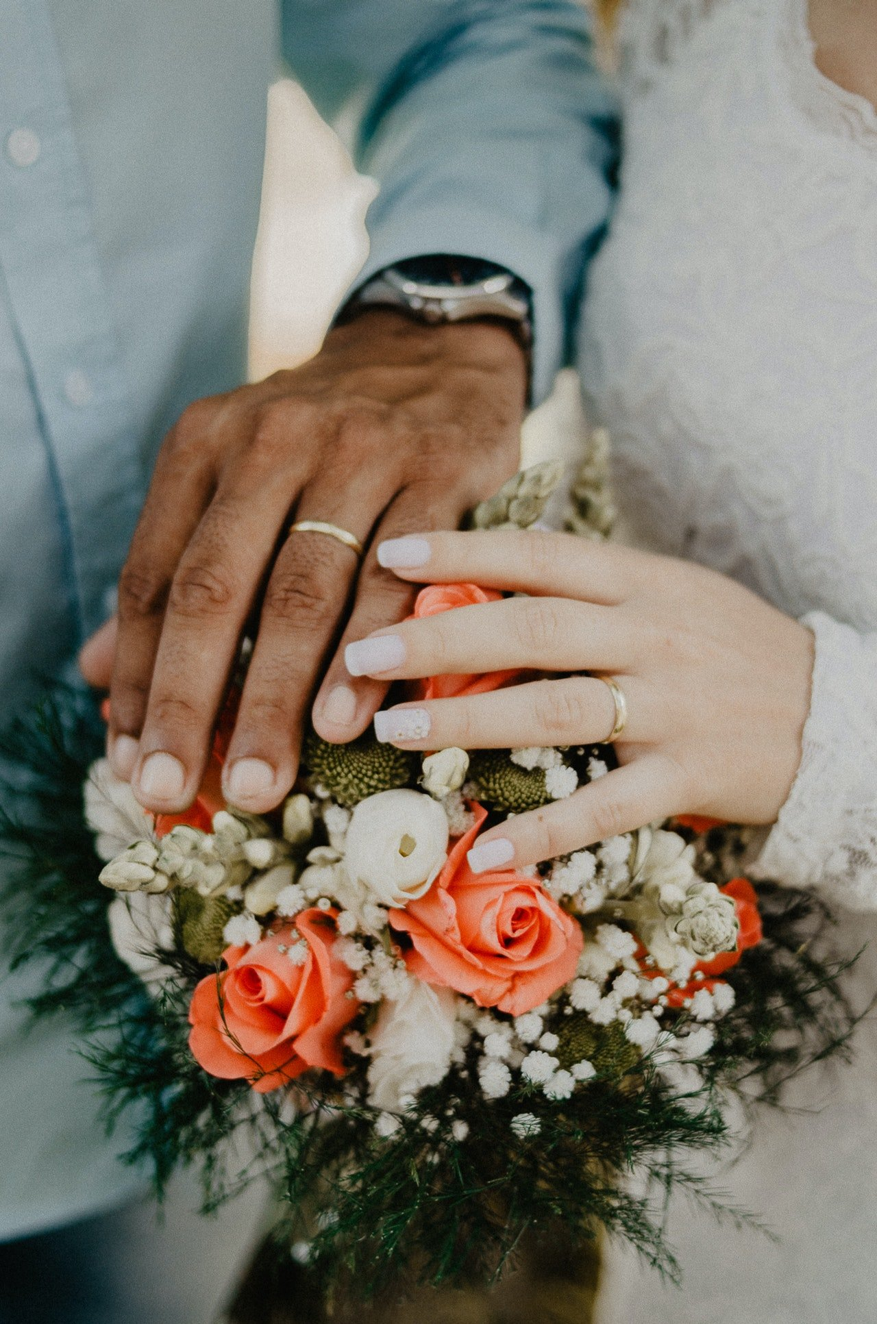Man and woman's hands on top of flower bouquet   Source: Pexels