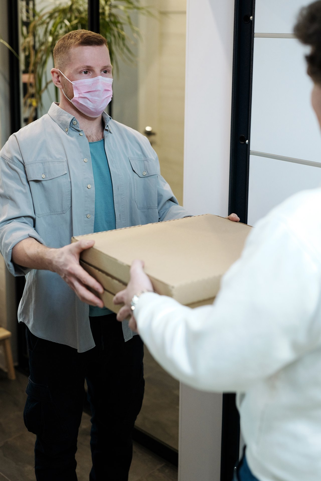 A man wearing a face mask receiving a Pizza delivery | Photo: Pexels