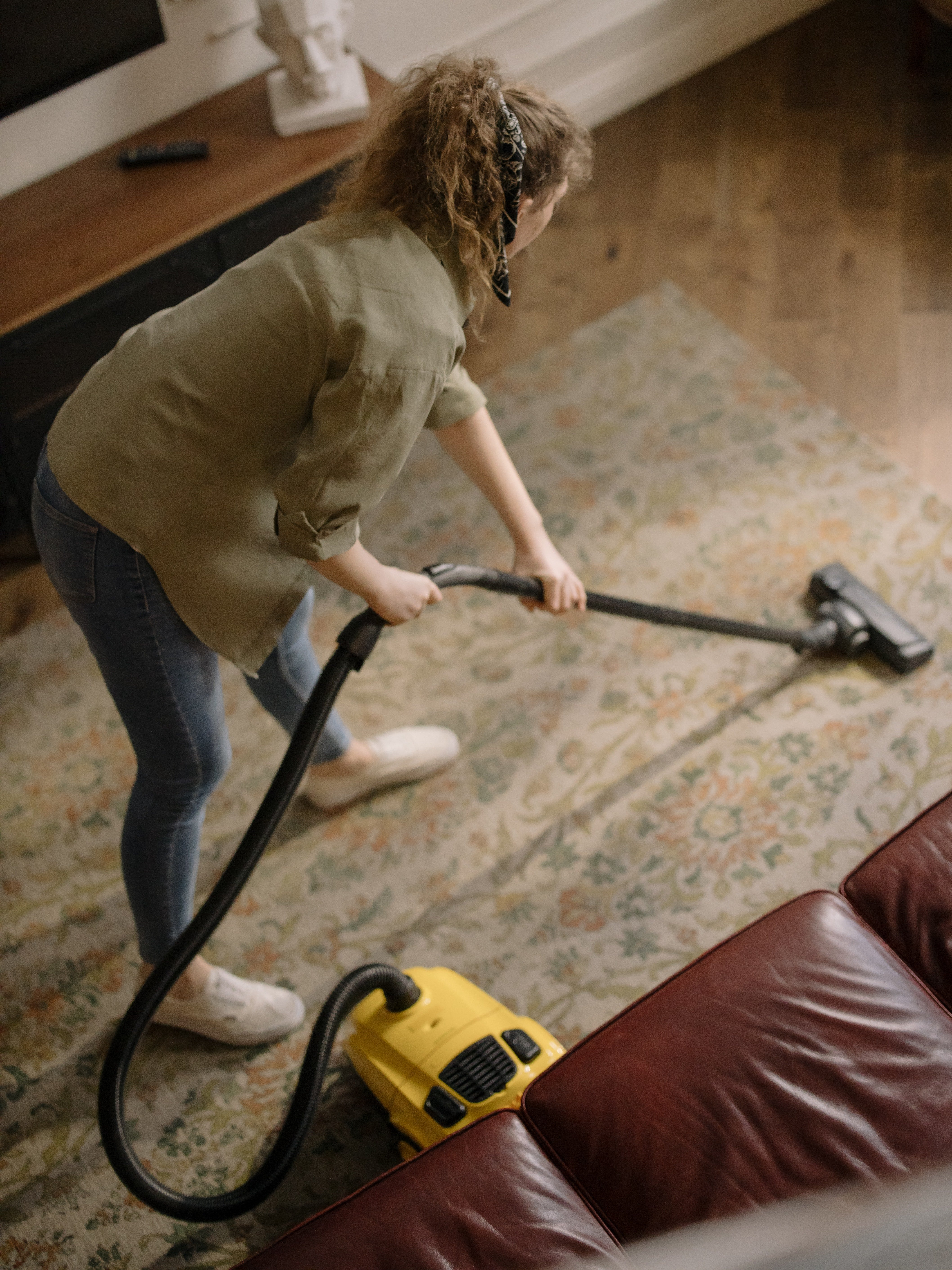 A lady vacuuming her home.   Pexels/ cottonbro