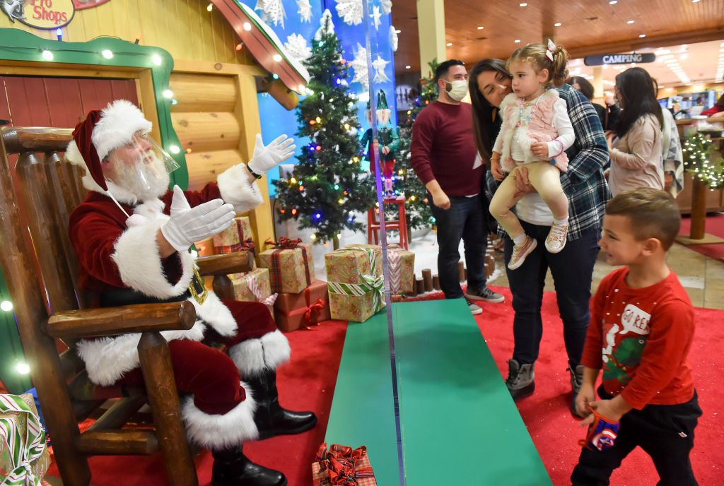 Santa Claus, wearing a face shield and separated by a plexiglass partition, interacts with Ashley Palermo, her daugher Leena, 2, and son Gio, 4, of Luzerne County, after getting their picture with Santa. At Cabela's in Tilden Township Friday evening on November 20, 2020 | Photo: Getty Images