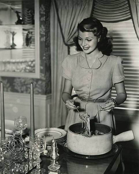 Rita Hayworth serves up spaghetti. In You'll Never Get Rich, 1941.   Source: Wikimedia Commons