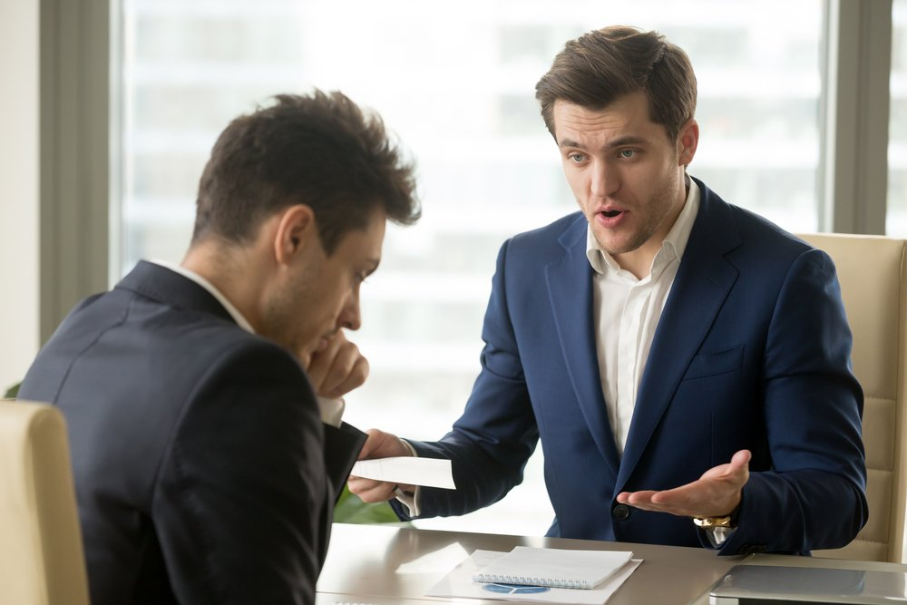 An angry mean boss yelling at an employee. | Photo: Shutterstock.