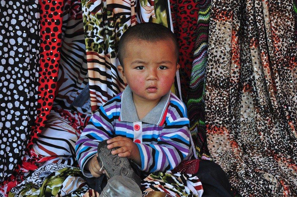 Un enfant assis dans des draps colorés | Image : Pixabay
