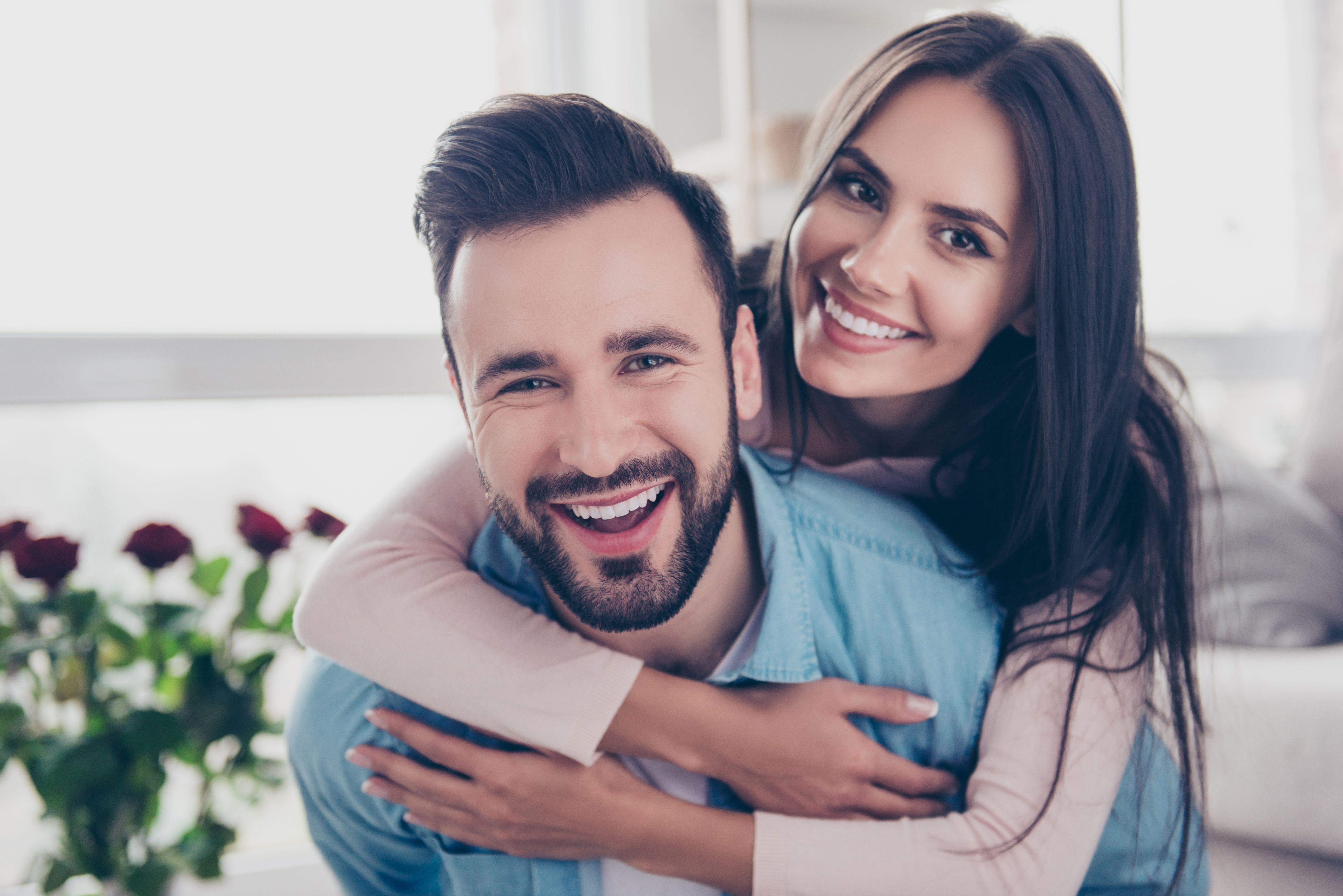 A couple smiling as the woman wraps his hands around her man. | Source: Shutterstock