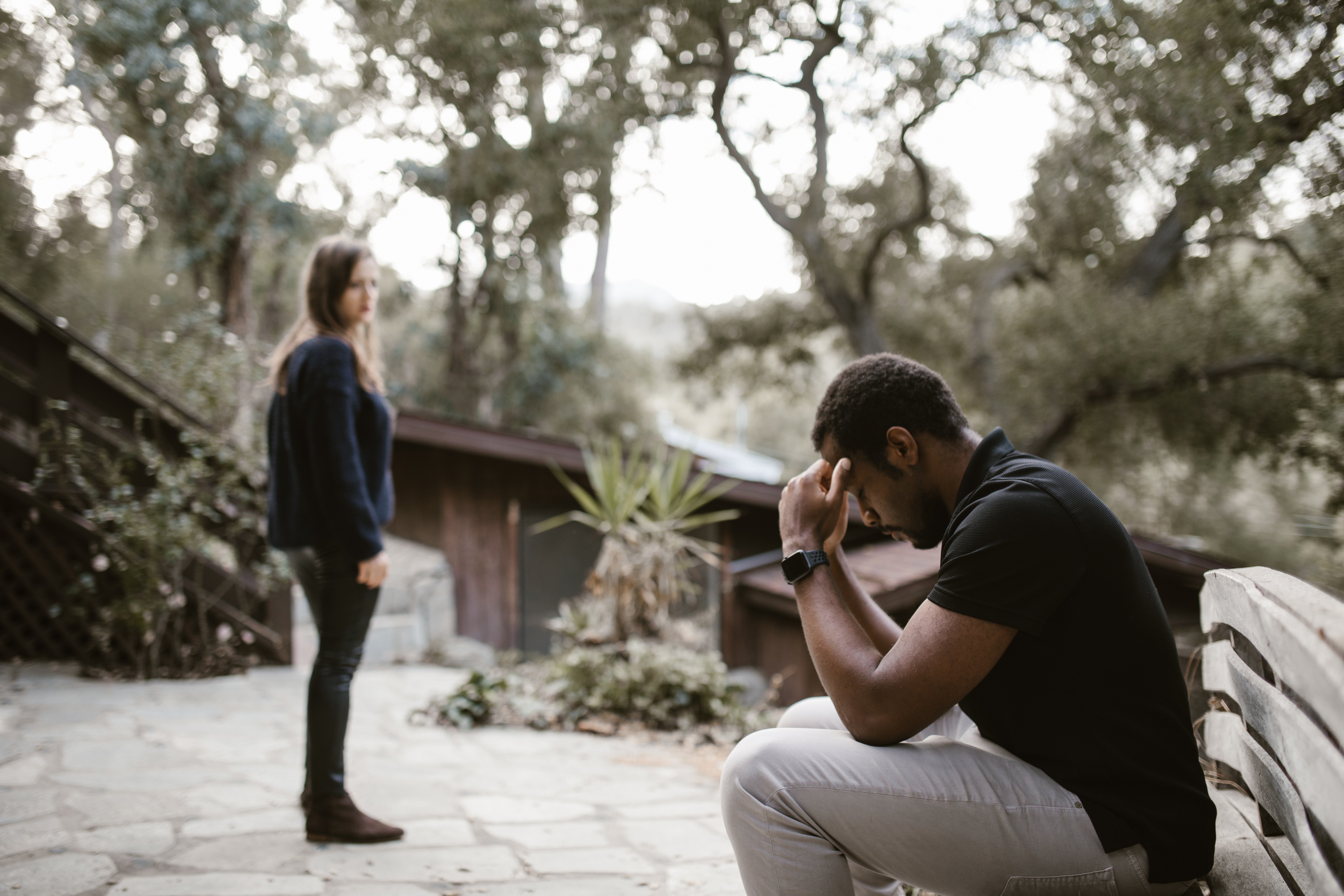 Pictured - A woman looking over a man sitting on a bench looking tense | Source: Pexels
