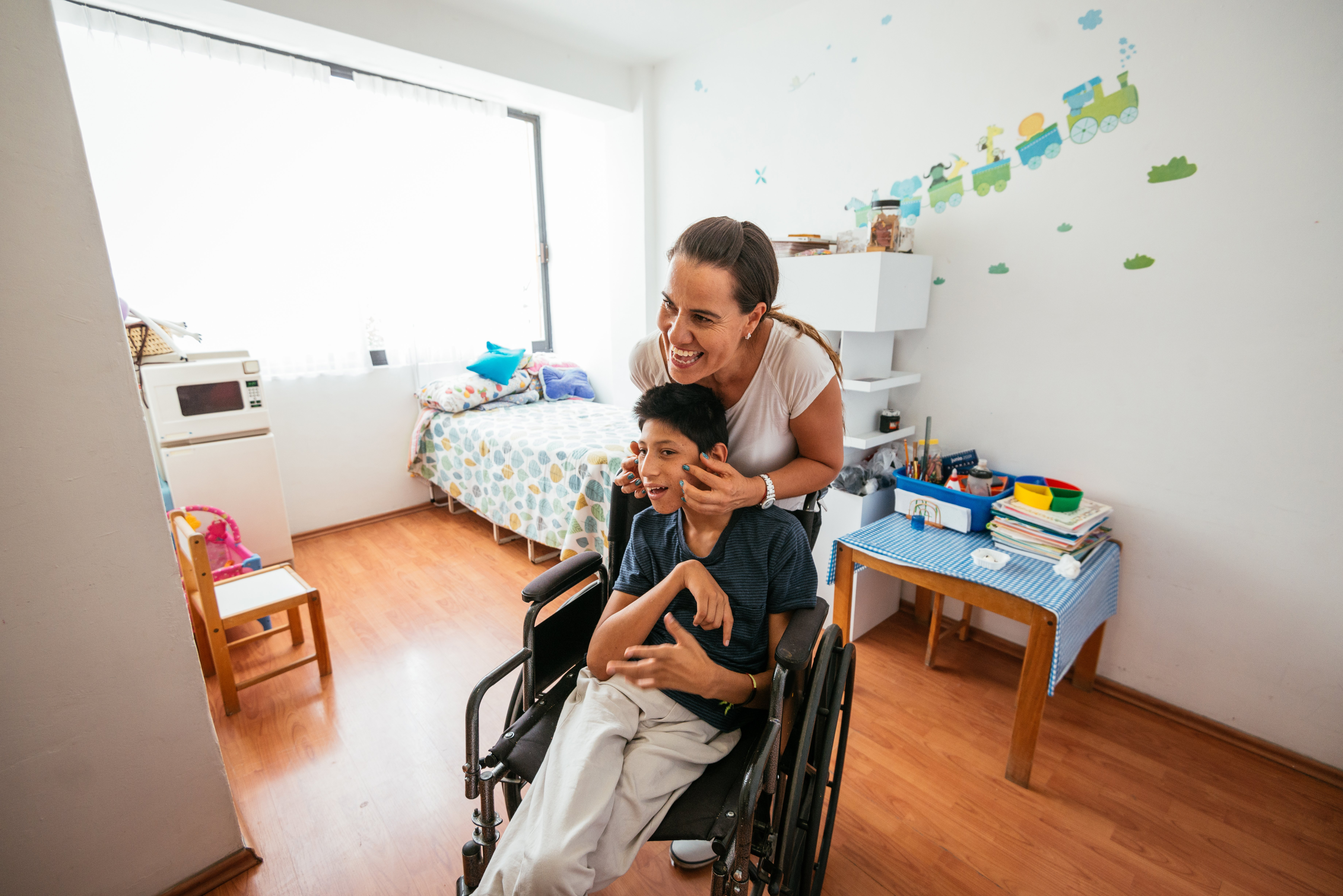 Latina mother massaging her son with Celebral Palsy|Photo: Getty Images