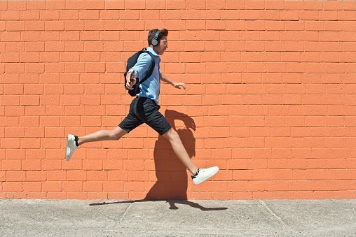 Teen student with backpack and headphone jumping and running to school | Photo: Getty Images