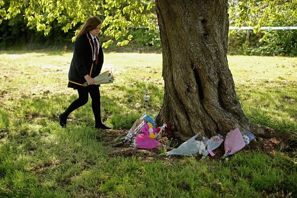 A local schoolgirl lays flowers where Amber Peat's body was found on June 3, 2015 in Mansfield, England.| Photo: Getty Images