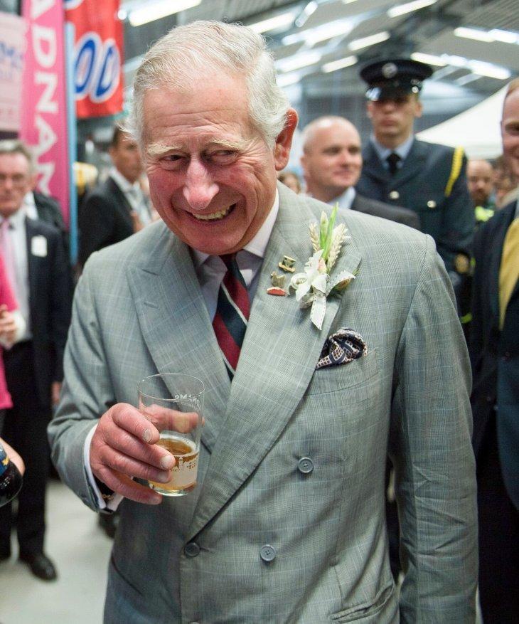 Le prince Charles souriant et tenant un verre dans un costume gris carreaux   Photo : Getty Images