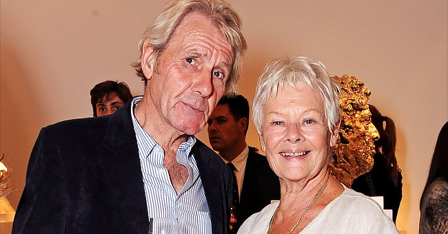 David Mills and Dame Judi Dench attend a private viewing for Nicole Farhi's debut exhibition of sculptures, 'From The Neck Up' at Bowman Sculpture on September 16, 2014 in London, England | Photo: Getty Images