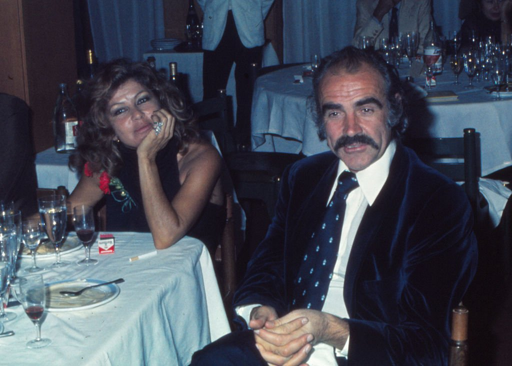 Sean Connery in the restaurant of the golf of 'La Manga del Mar Menor' with his wife Micheline Roquebrune, 1973, Murcia, Spain | Photo: Getty Images