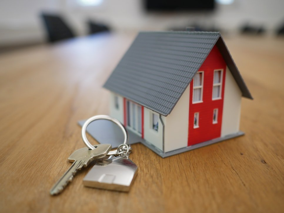 A photo of a house and keys on a table.   Source: Unsplash