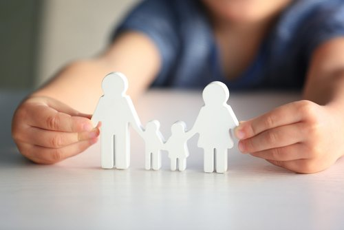 Child holding figure in shape of happy family. | Source: Shutterstock