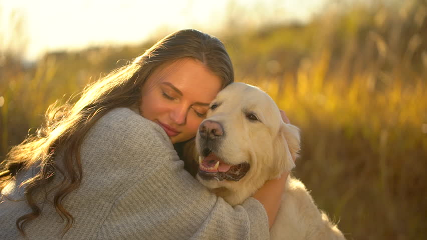 Pretty young woman hugging her dog | Photo: Shutterstock