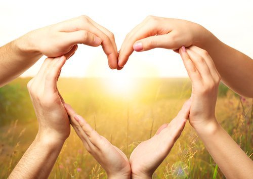 Heart shaped by hands with nature background. | Source: Shutterstock.