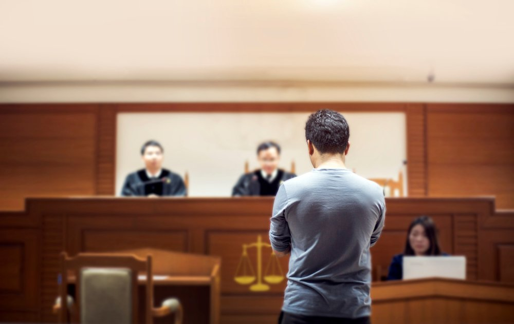 An accused man talking to magistrate in court. | Photo: Shutterstock.