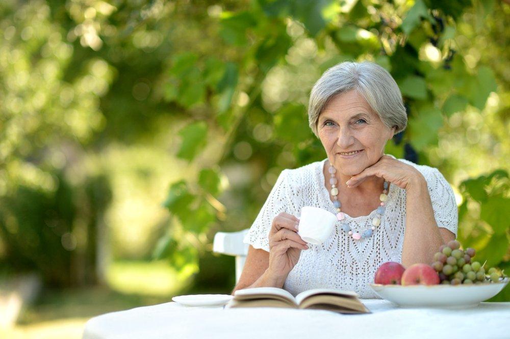 Retrato de una bella mujer de mayor edad al aire libre en una mesa. Fuente: Shutterstock