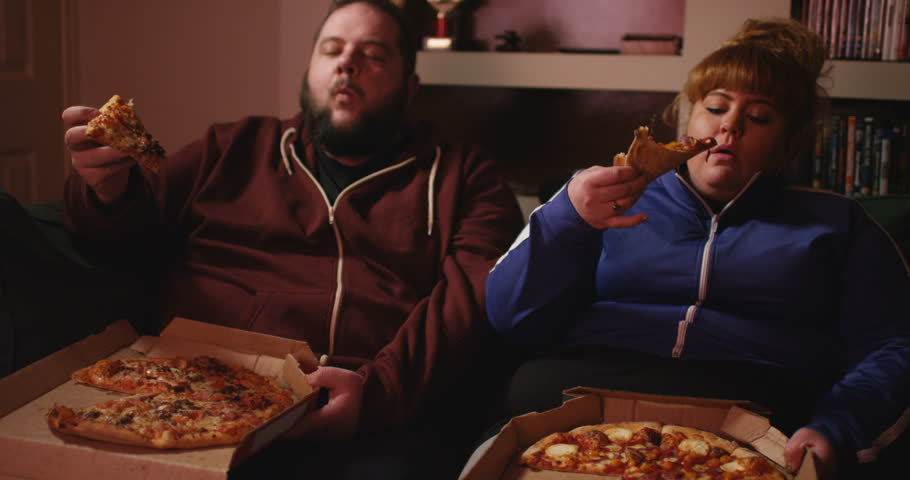 An overweight couple, eating pizza in their living room | Source: Shutterstock.com