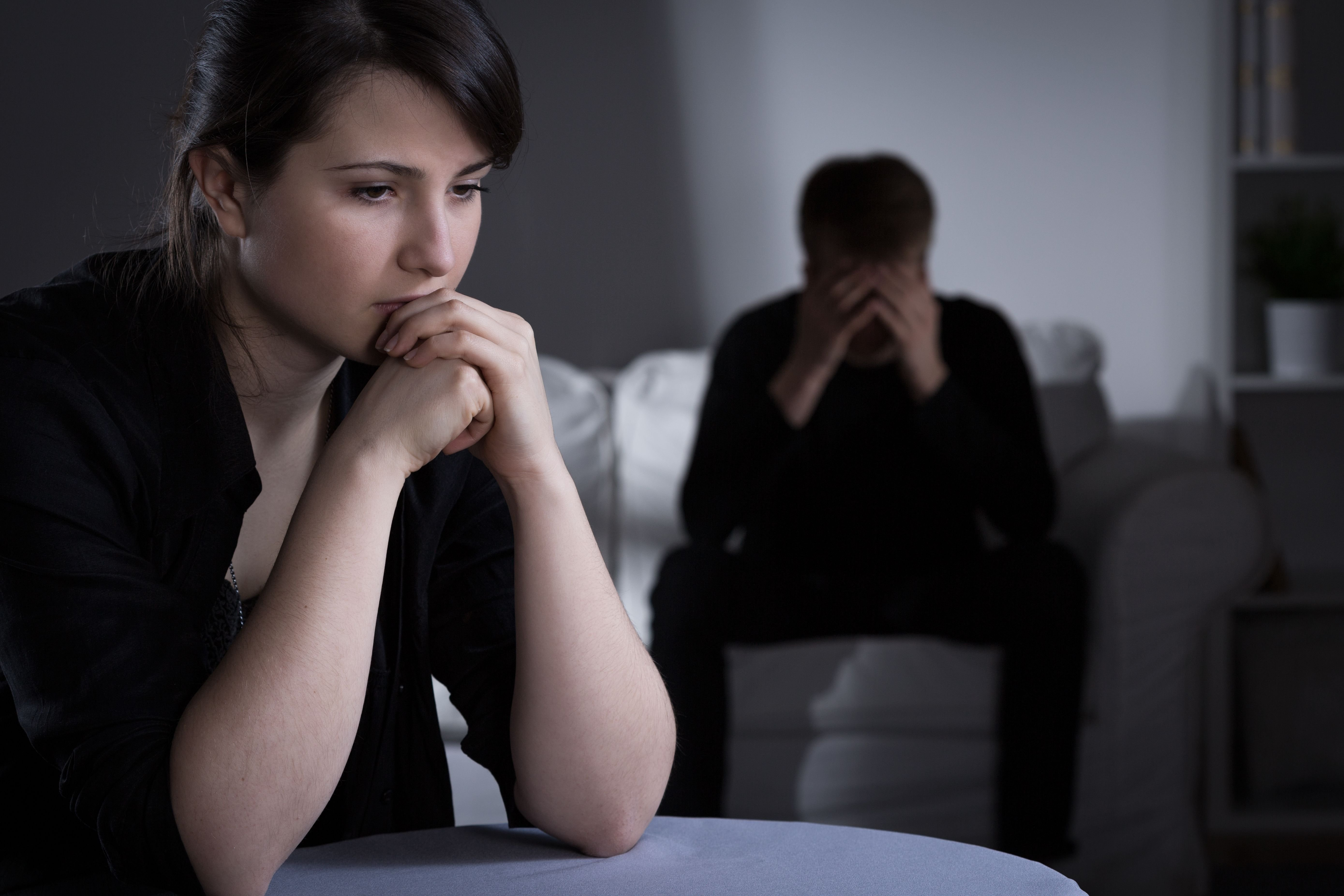 A woman looks in deep thought while a man sits behind her. | Source: Shutterstock