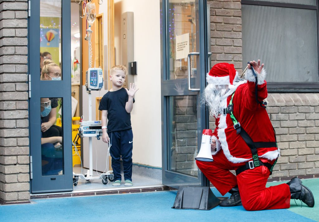 A man dressed as Santa Claus kneels outside the building as he speaks to Ellis Harkin through an open doorway as he visits patients at Leeds Children's Hospital on Mon. December 21, 2020  | Photo: Getty Images