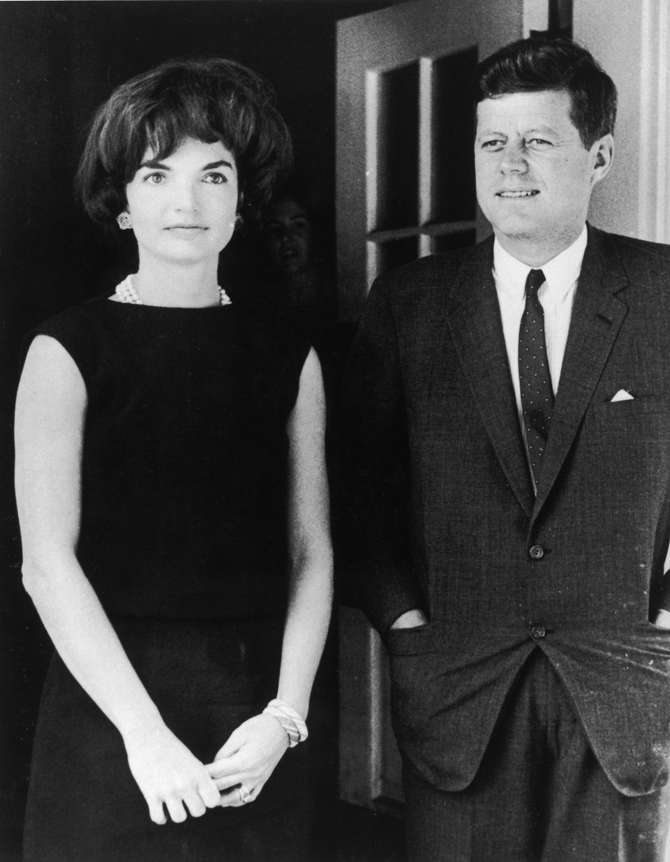 Jacqueline Kennedy (1929 - 1994) stands with her husband, President John F. Kennedy (1917 - 1963), in the door of the White House, Washington, D.C., circa 1961. | Source: Getty Images