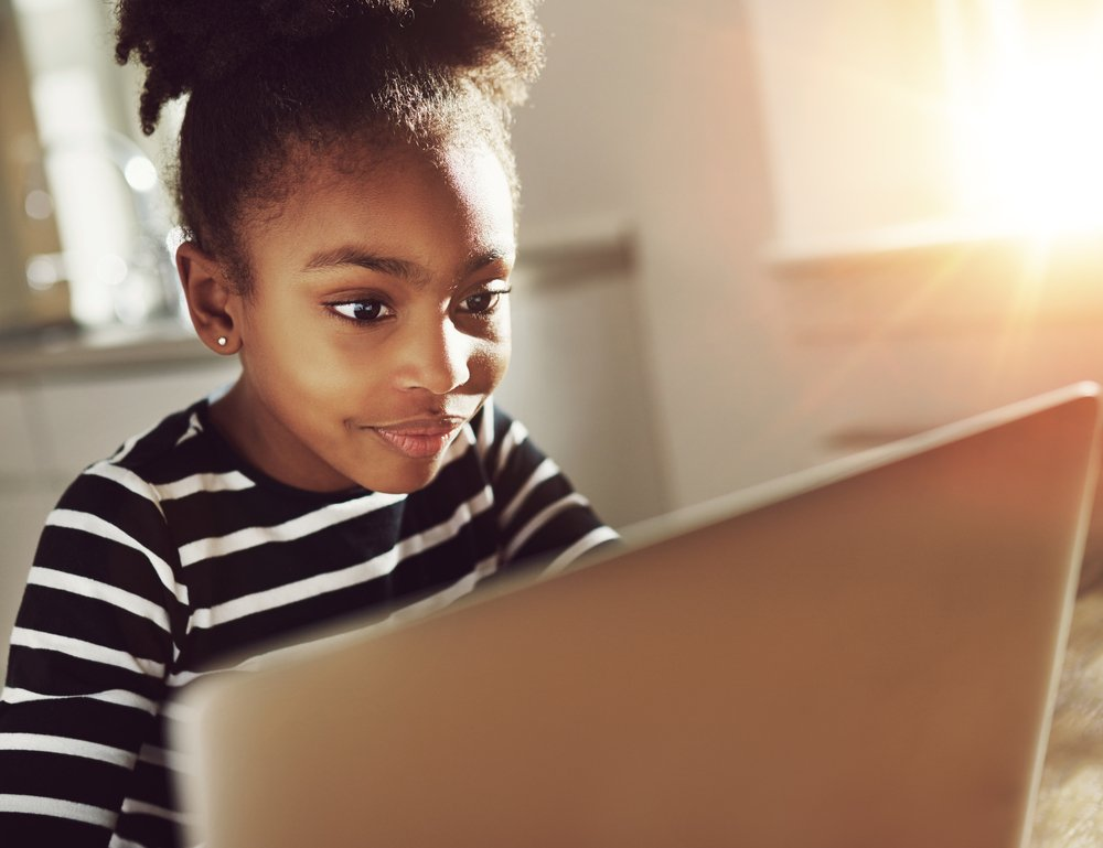 Smiling young girl is absorbed in laptop use | Photo: Getty Images