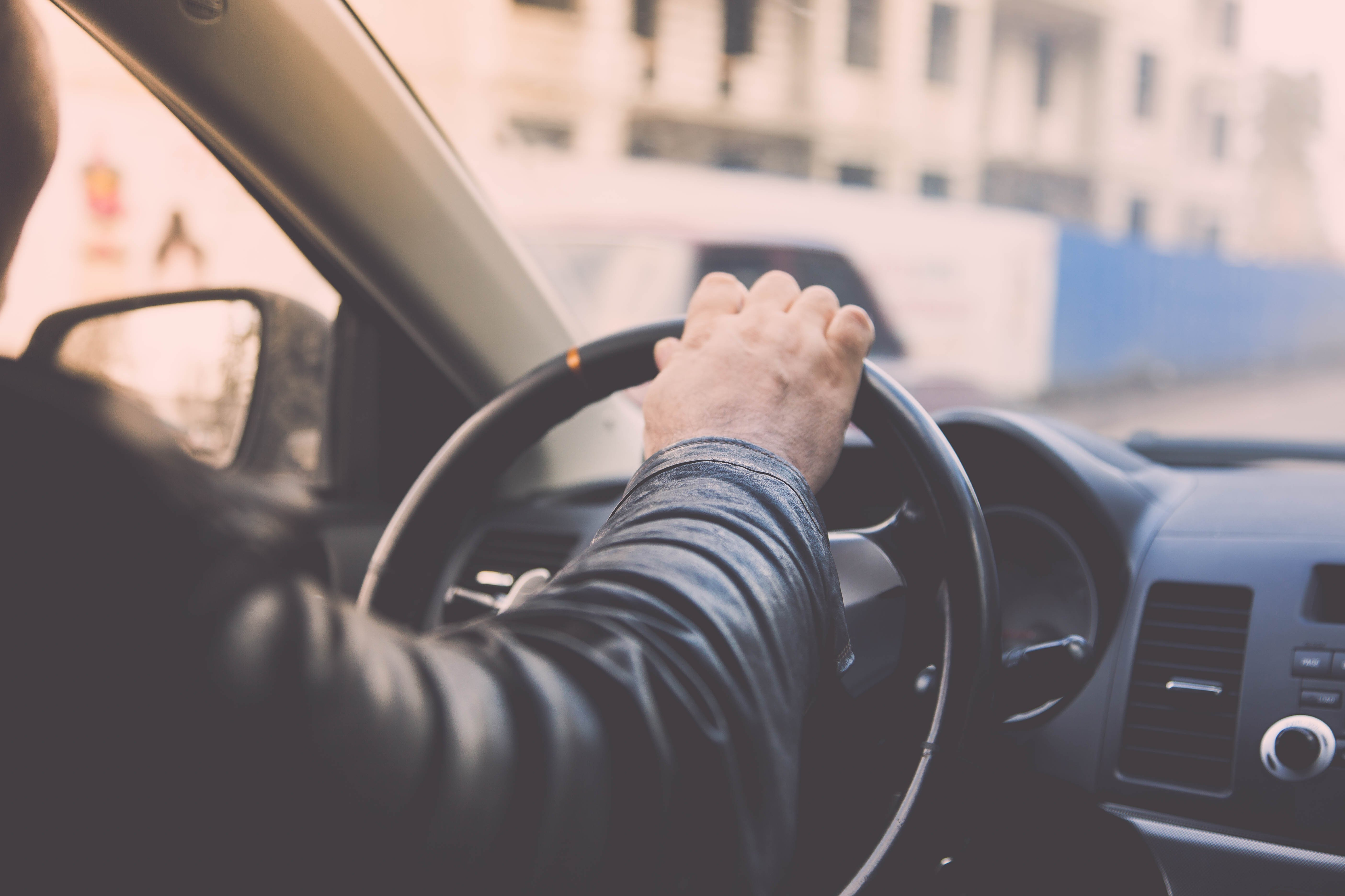 Taxi driver driving car, hand on steering wheel, looking at the road | Photo: Shutterstock.com