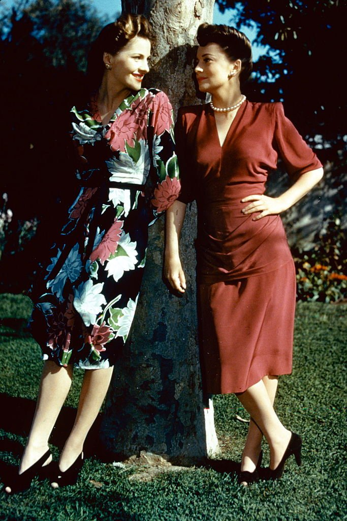 Full-length portrait of Joan Fontaine (left) and her sister, Olivia de Havilland, both British actress, standing in conversation by a tree, circa 1945. | Source: Getty Images