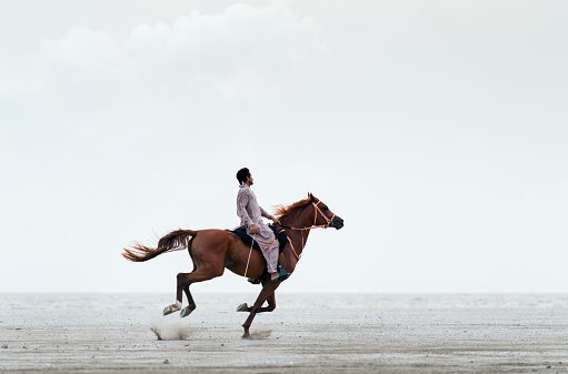 Photo of a man riding a horse on sand against a clear sky | Photo: Getty Images