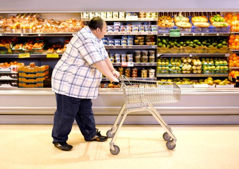 Photo of overweight man passing by healthy food in supermarket | Photo: Getty Images