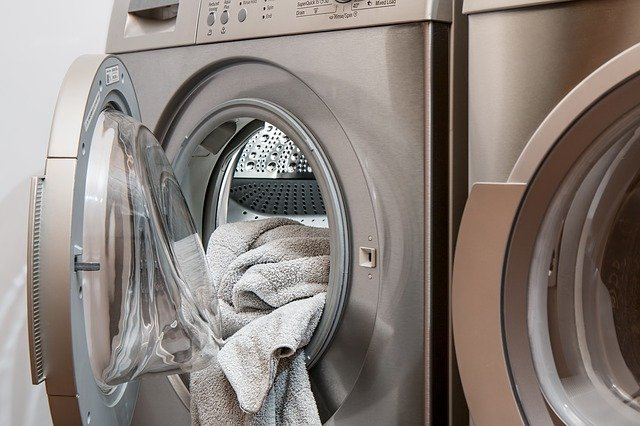 Clothes hanging out of a washing machine. | Source: Pixabay