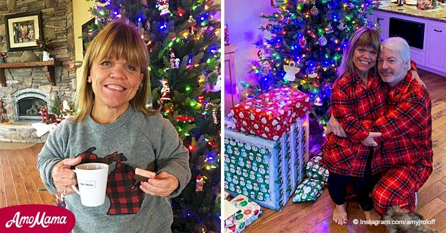 Amy Roloff hugs her boyfriend wearing matching pajamas posing under a sparkling Christmas tree