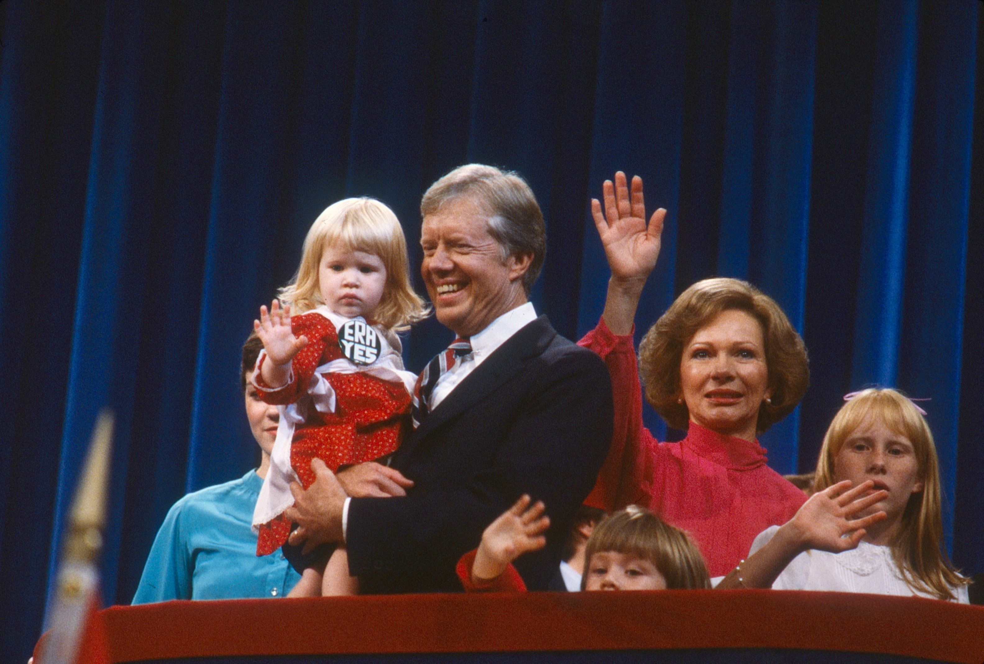 President Jimmy Carter, holding his grand-daughter Sarah Carter, First Lady Rosalynn Carter (in red), and their daughter, Amy Carter during the 1980 National Democratic Convention held at Madison Square Garden, New York, New York, August 11-14, 1980.  Source: Getty Images