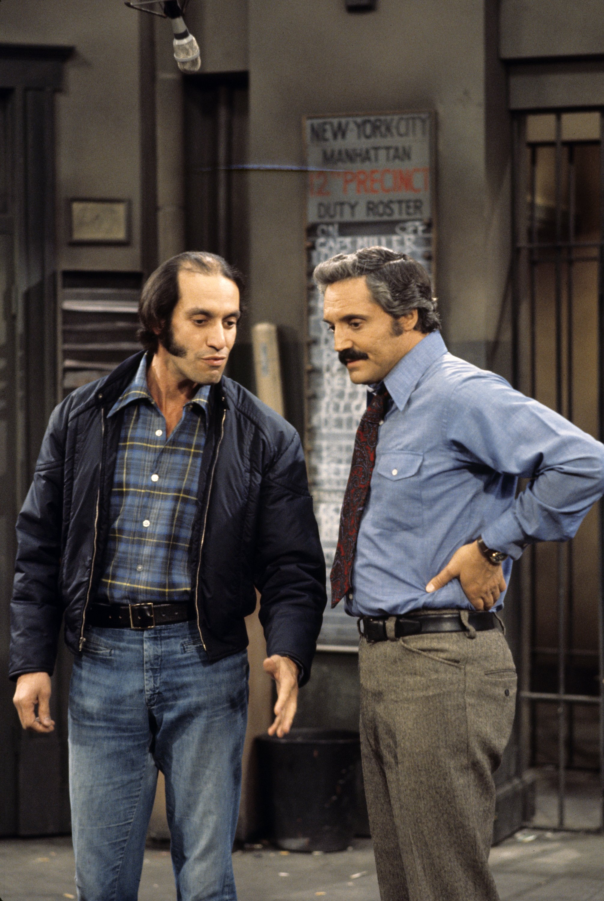"""Gregory Sierra (left) and Hal Linden (right) on the set of """"Barney Miller"""" which premiered in 1975. 