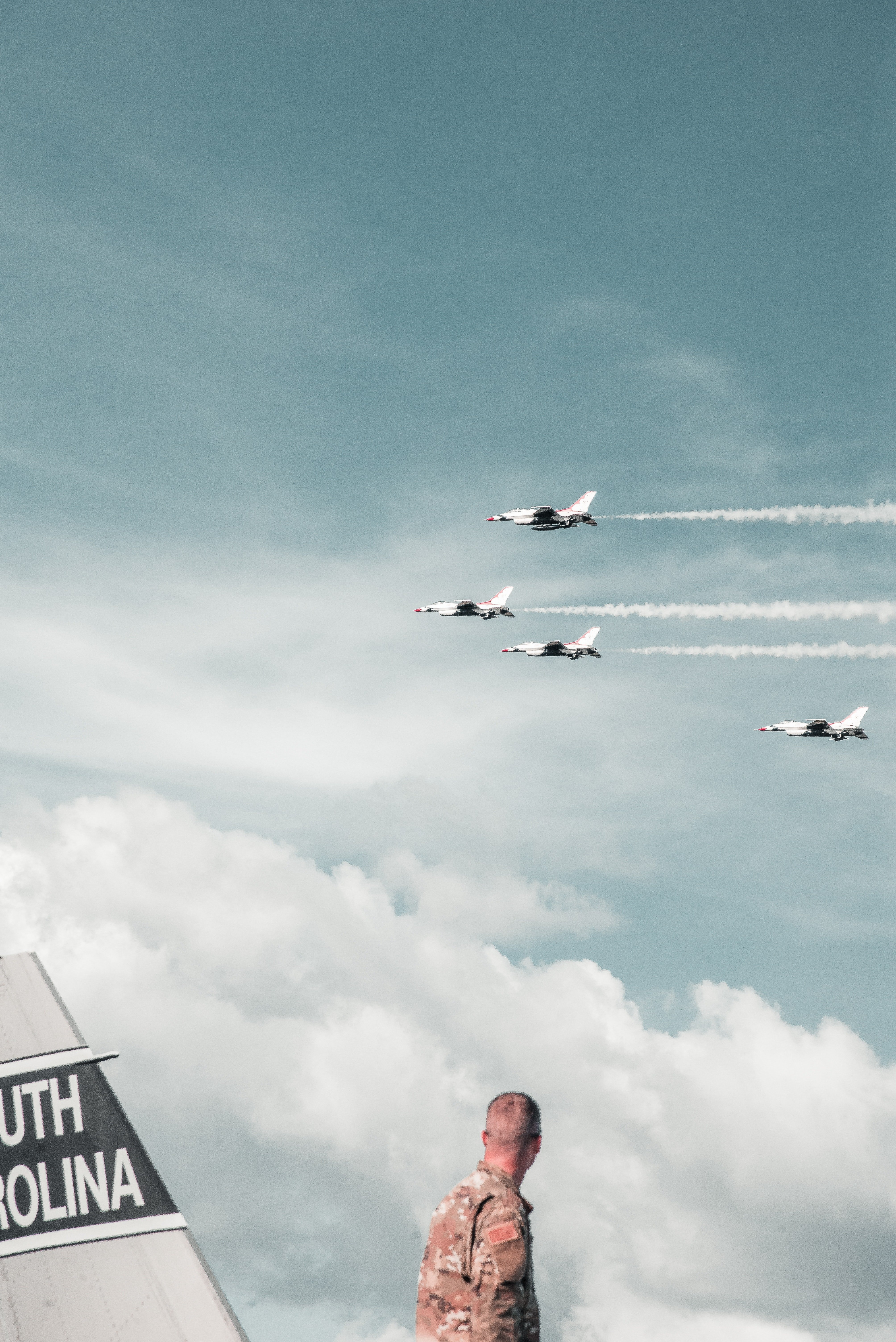 Pictured - A soldier looking over at four fighting jets flying | Source: Pexels