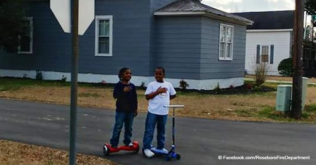 Boys stop to declare Pledge of Allegiance next to a flag outside North Carolina fire dept.