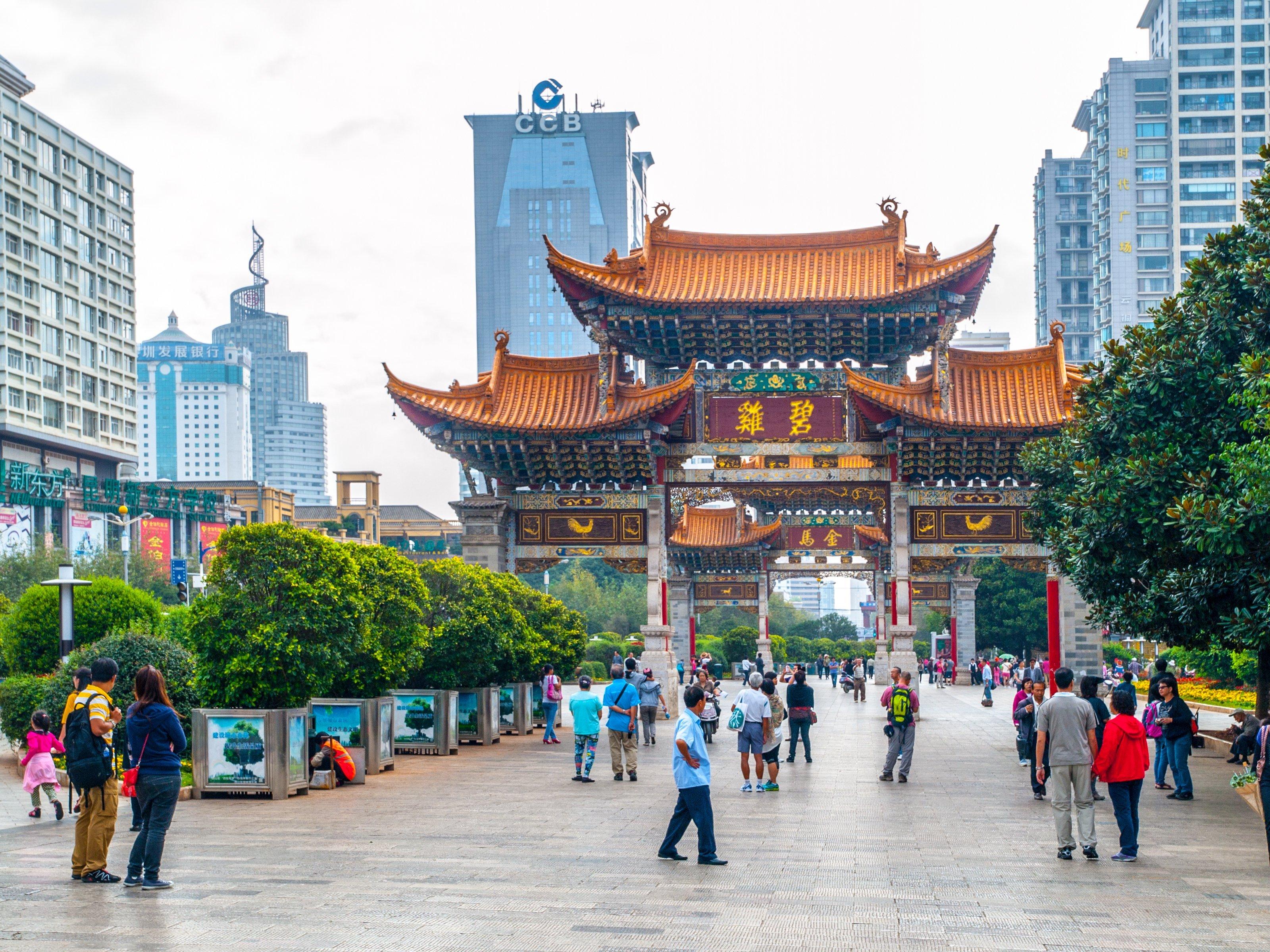 Arco de Kunming. Puerta tradicional china y edificios modernos del centro de la ciudad, Kunming, provincia de Yunnan, China. Fuente: Shutterstock