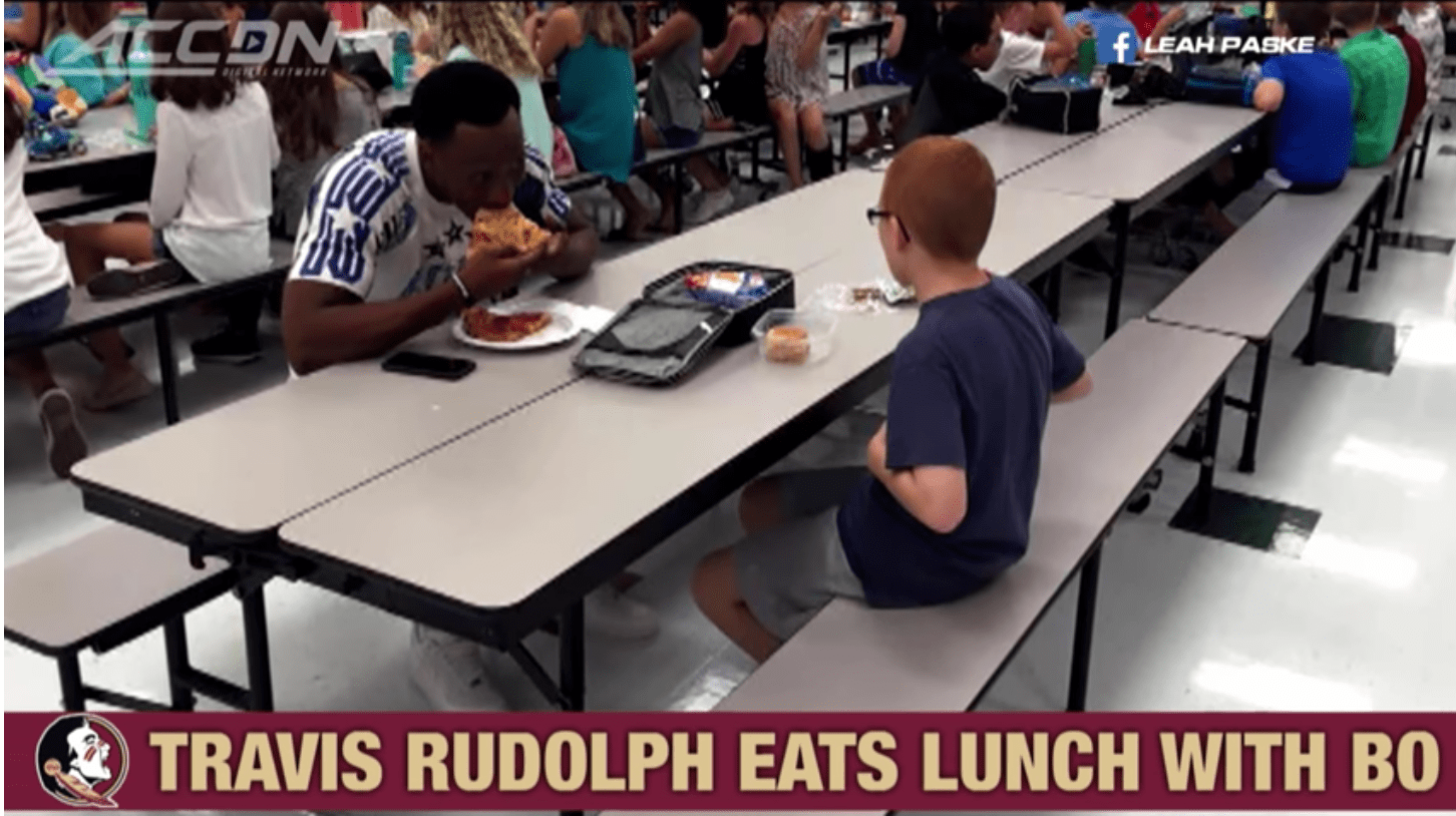 Screenshot of photo of Travis Rudolph sitting with Bo Paske at Montford Middle School in Tallahassee, Florida, 2016. | Source: Youtube/ACC Digital Network