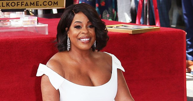 Niecy Nash Sizzles in Tight Black Jumpsuit with Animal Print Jacket and Matching Boots in a Photo