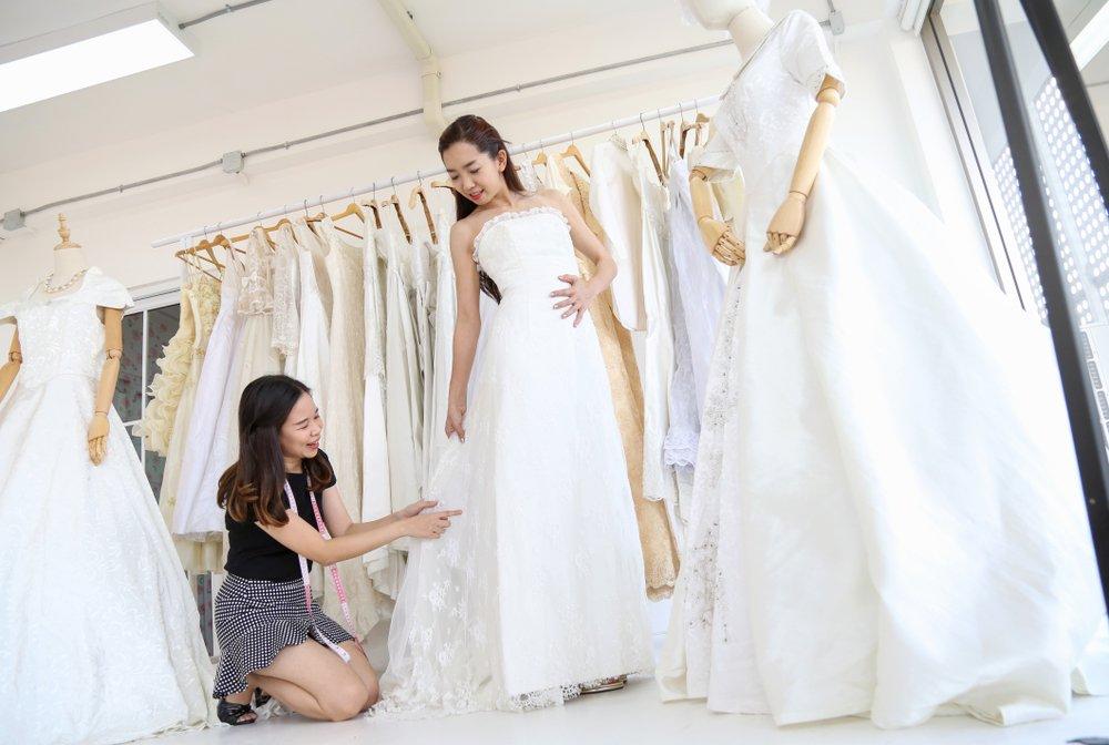 Une couturière aide la mariée dans l'essayage de la robe de mariée blanche au studio. | Shutterstock