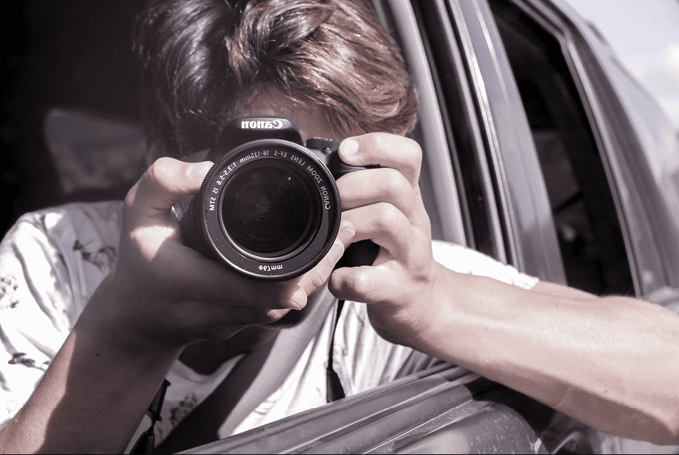 A private investigator taking pictures with a camera from a car   Photo: Pixabay