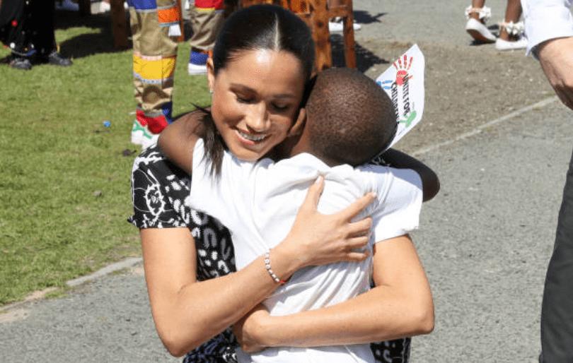 Au cours de sa tournée en Afrique avec le prince Harry, Meghan Markle embrasse un jeune à l'initiative Justice Desk dans le township de Nyanga, le 23 septembre 2019, au Cap, en Afrique du Sud | Getty Images