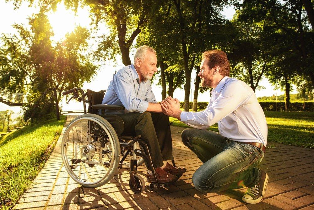 Un jeune homme et son vieux père en fauteuil roulant dans un parc. | Shutterstock