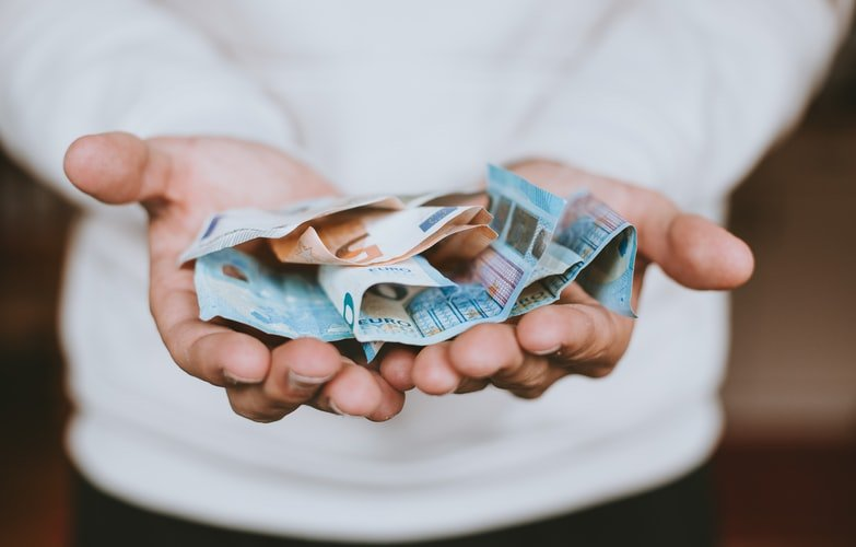 A photo of a man with his hands stretched asking for money. | Photo: Unsplash