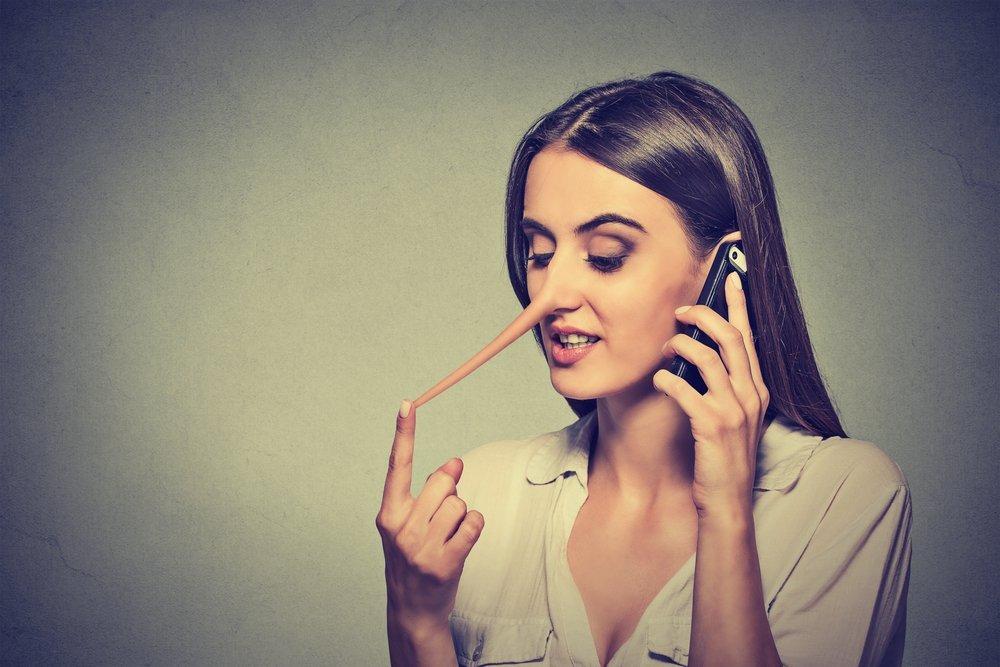 Portrait de jeune femme disant des mensonges sur portable. | Shutterstock