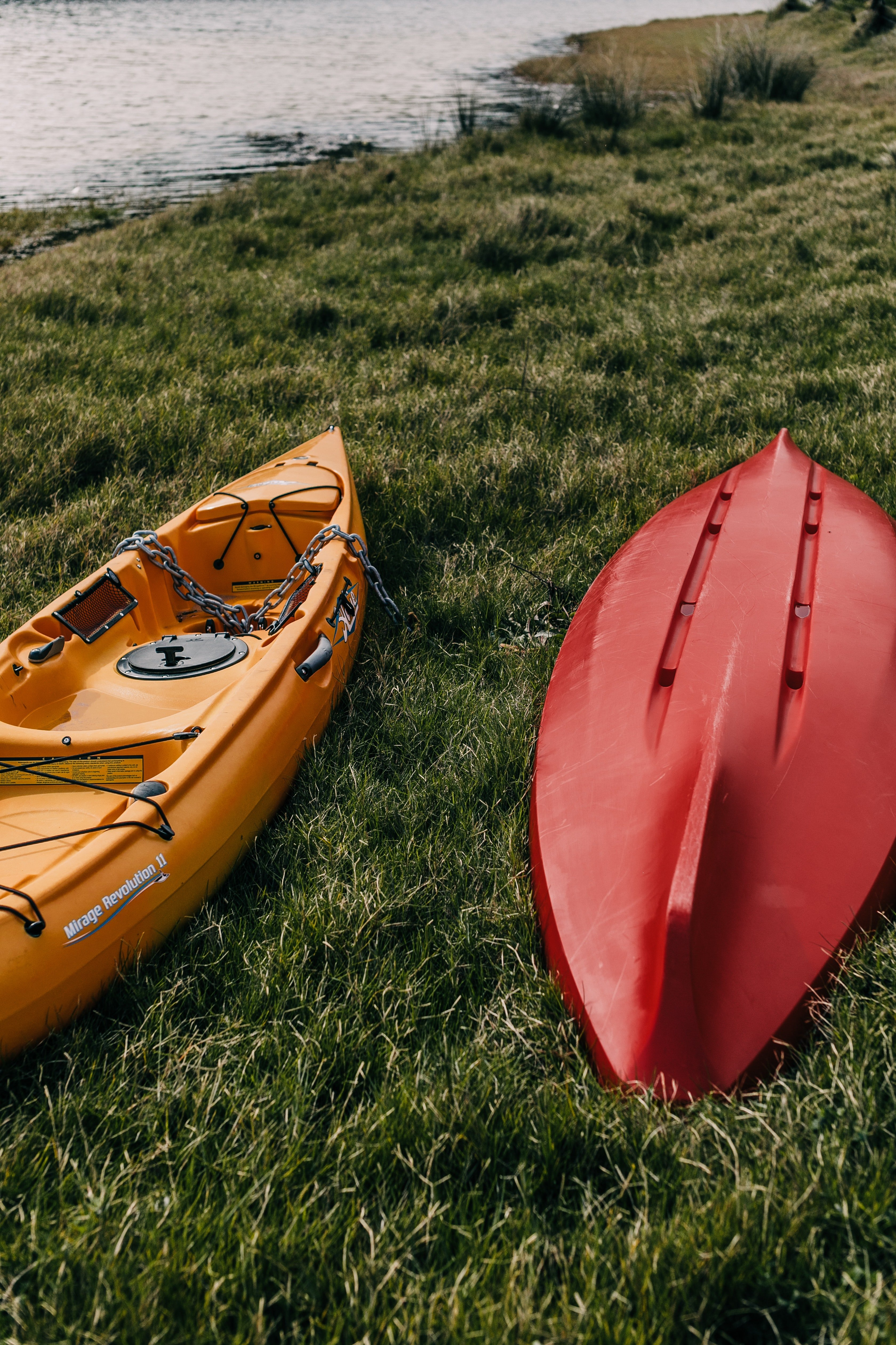 A red and yellow canoe lying on the grass. | Photo: pexels