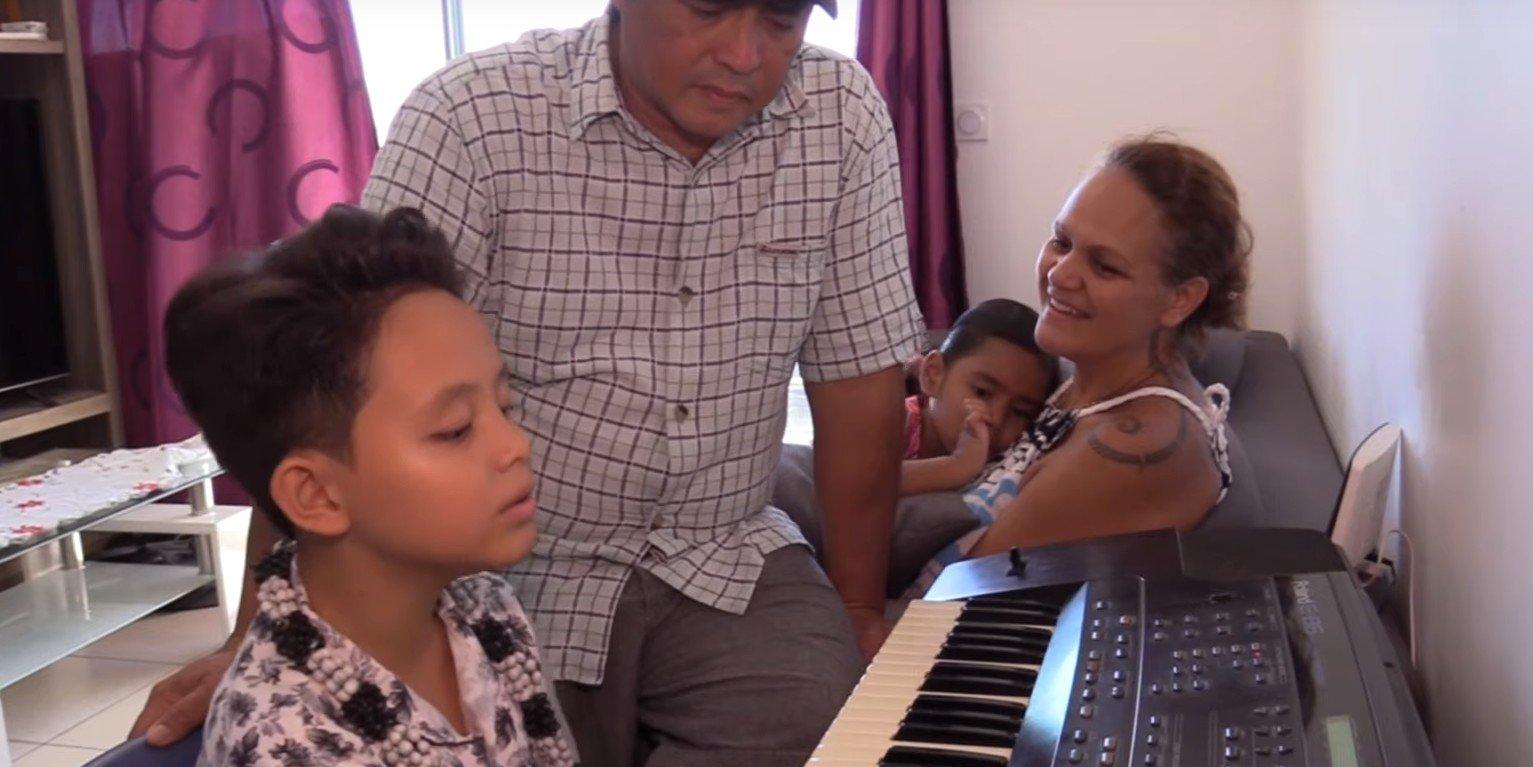 Natihei jouant du piano et chantant pour le plus grand plaisir de sa famille. l Source : YouTube/Tahiti Nui Télévision