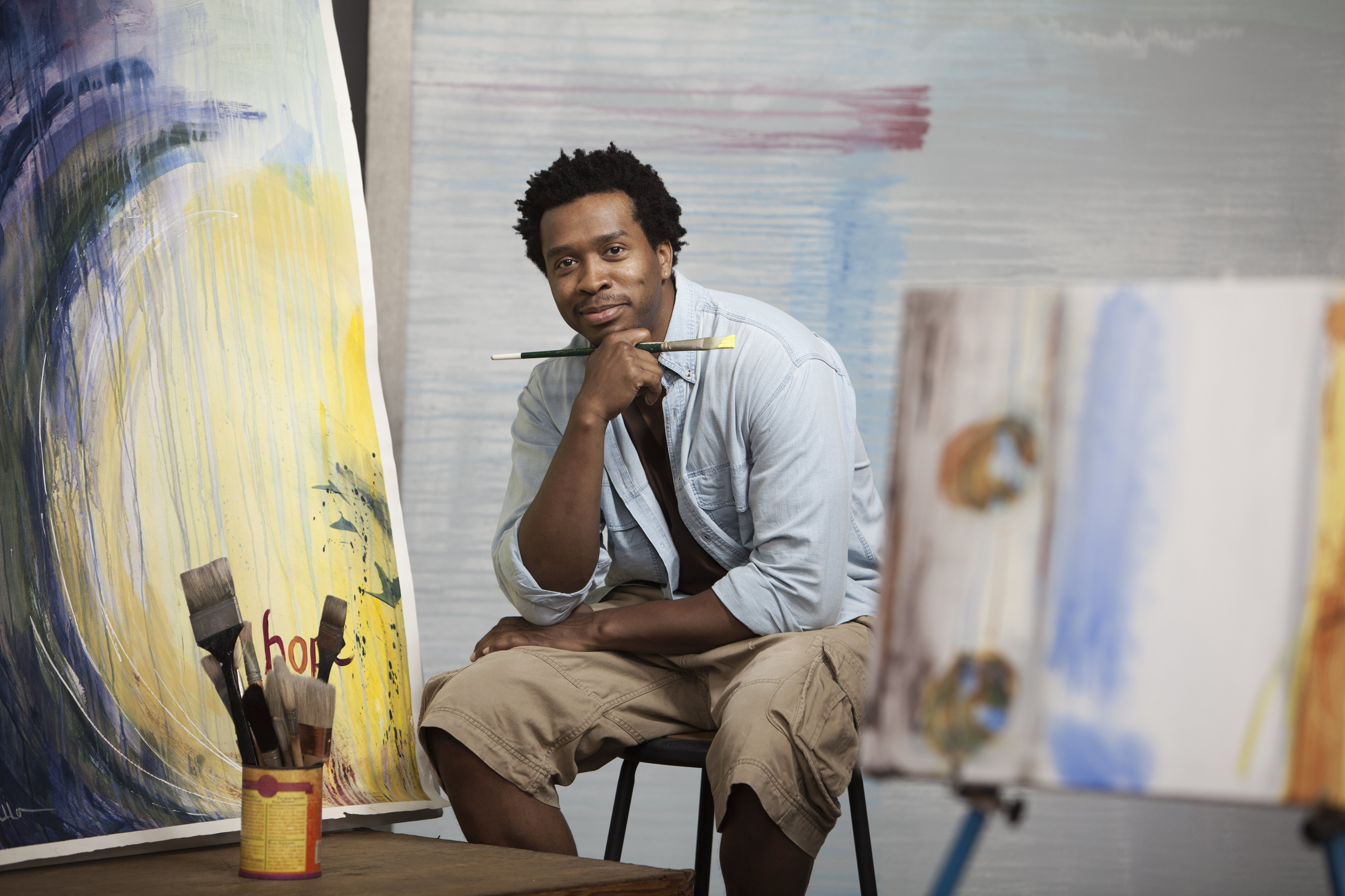 A black Artist sitting in studio as he poses for a photo | Photo: Getty Images